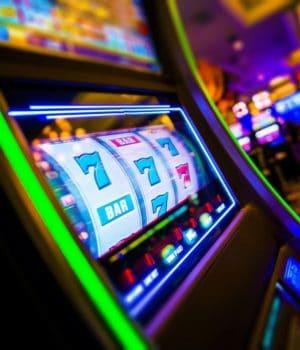 Spielautomat bzw. Einarmiger Bandit im Vordergrund innerhalb eines Casinos